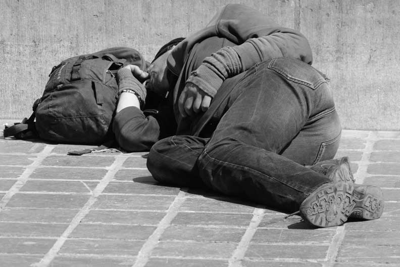 Homeless man sleeping in the street